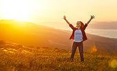 istock Happy woman   on sunset in nature iwith open hands 914602060
