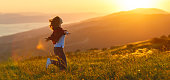 istock Happy woman   on sunset in nature iwith open hands 924467840