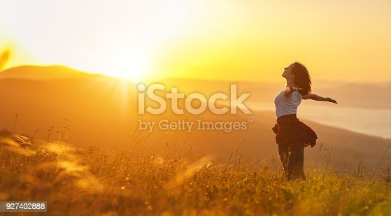 istock Happy woman   on sunset in nature iwith open hands 927402888