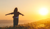 istock Happy woman   on sunset in nature iwith open hands 931869408