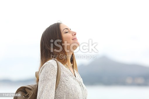 Happy woman on the beach breathing fresh air