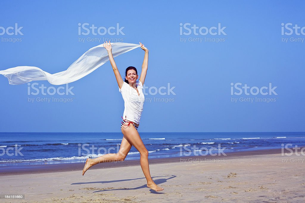 Happy woman on the beach Happy woman running on the tropical beach, holding white shawl in her hands with wind blowing. Looking at camera and smiling. 25-29 Years Stock Photo