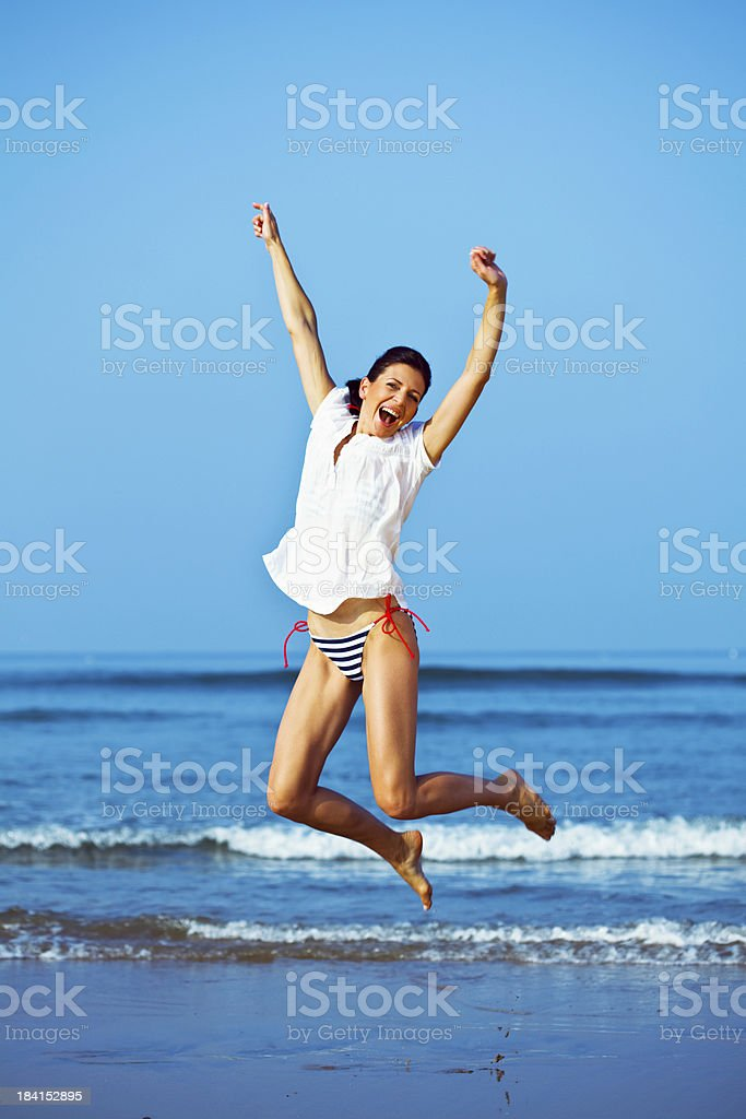 Happy woman on the beach Happy woman jumping on the tropical beach with arms outstretched. Looking at camera and laughing. 25-29 Years Stock Photo