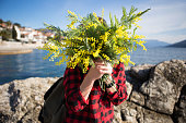 Happy woman on the beach with a bouquet of mimosa flowers. The girl covers her face with a bouquet of yellow flowers.