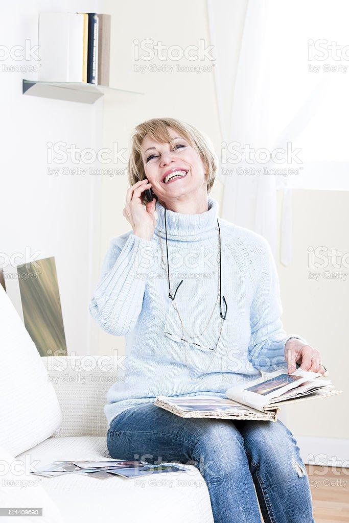 Glückliche Frau am Telefon suchen nach Photoalbum – Foto