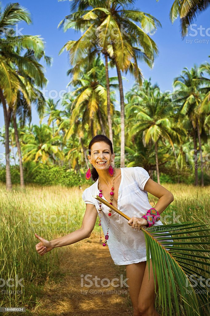 Happy woman on tropical vacation Smiling woman on tropical vacation standing in hitch-hiking pose and holding palm leaf in her hand. Coconut palm trees and blue sky in the background. 30-34 Years Stock Photo