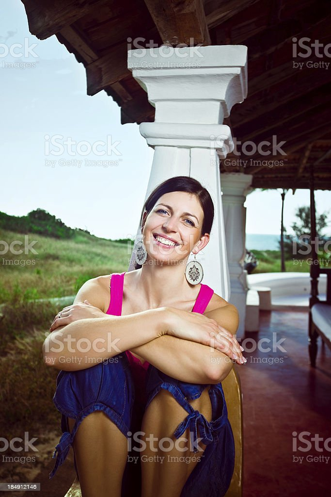 Happy woman on tropical vacation Woman enjoying tropical vacation, sitting on rustic veranda and smiling at camera. Coaastline in the background. 30-34 Years Stock Photo