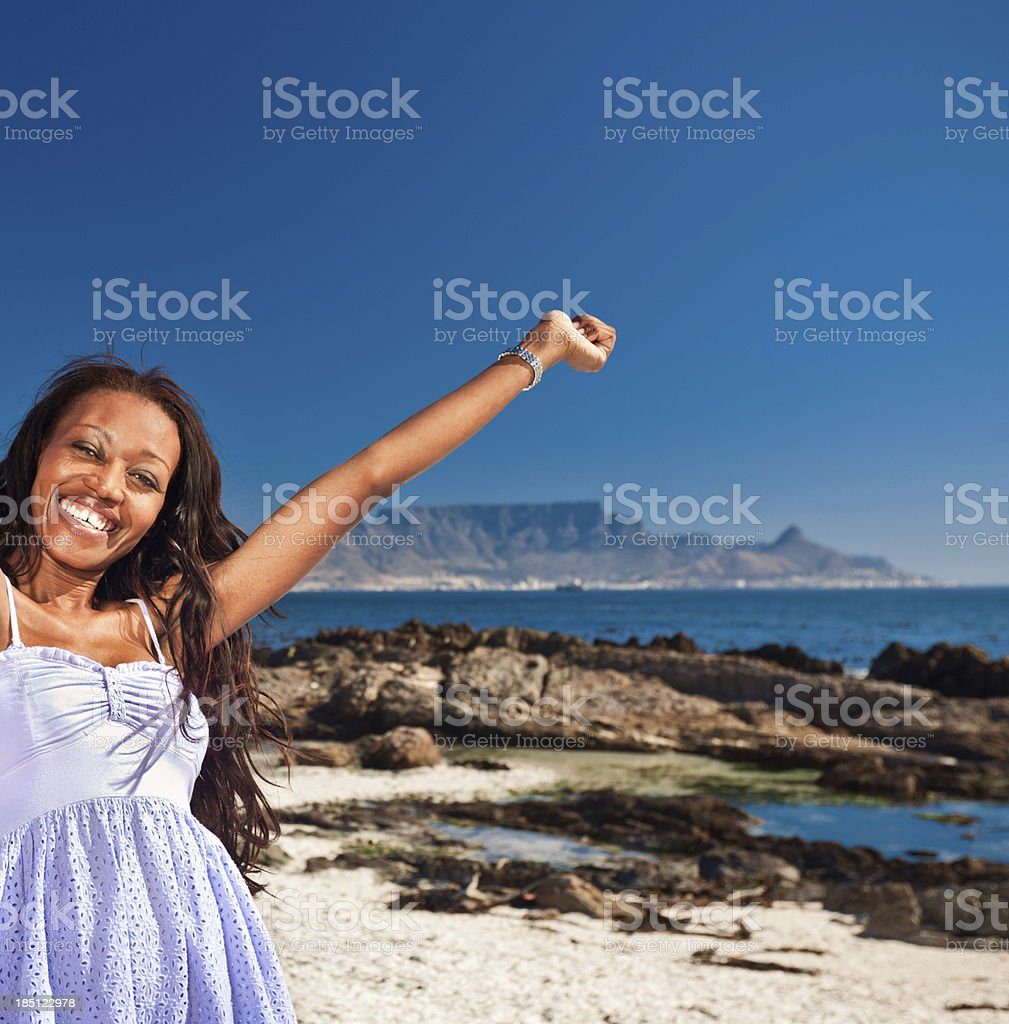 Happy woman on vacation Happy african american woman raising her hands against the Table Mouintain in the background. Smiling at the camera. Adult Stock Photo