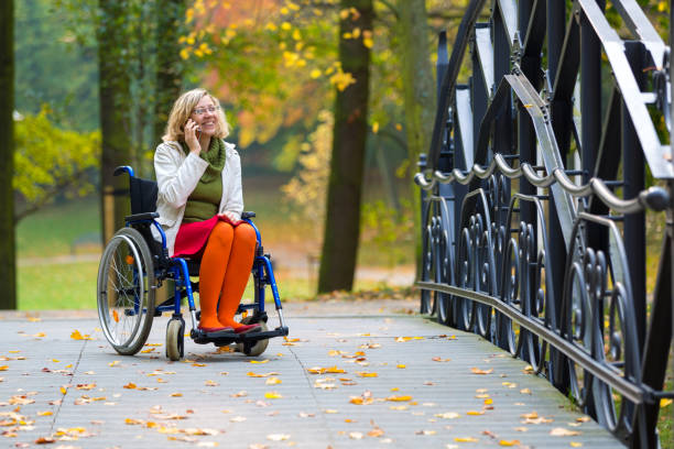 happy woman on wheelchair talking on the phone stock photo