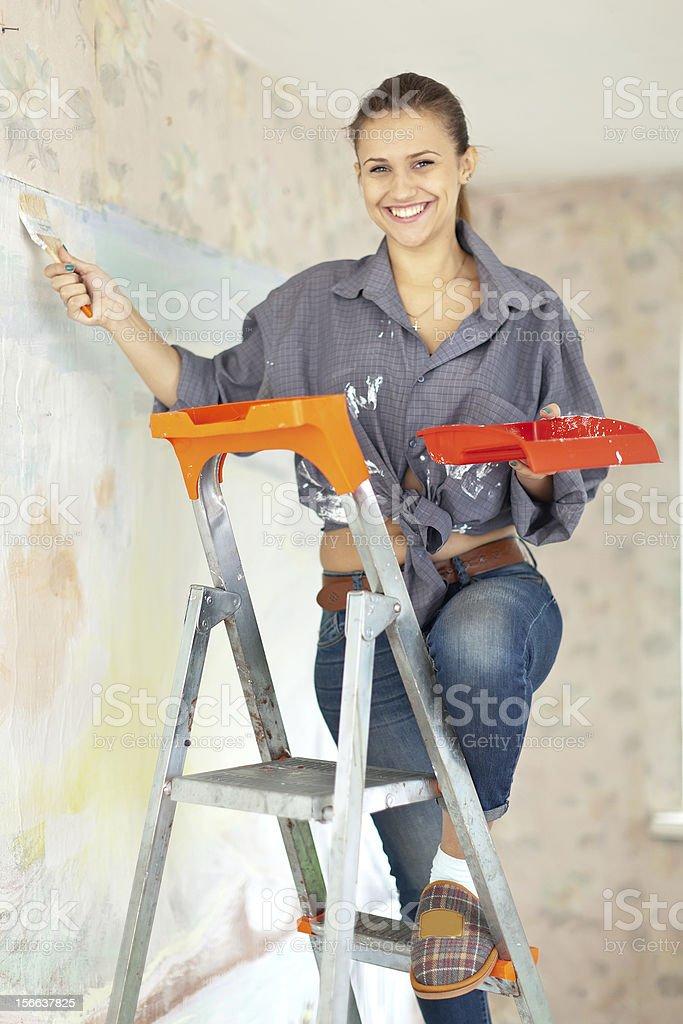 Happy woman paints wall stock photo
