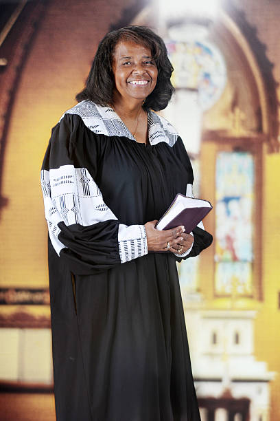 Happy Woman Pastor A  senior-adult woman in her black and white pastoral robe inside an old English Gothic church. clergy stock pictures, royalty-free photos & images