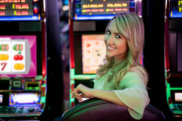 Happy woman playing at the casino Happy woman playing at the casino on the slot machines and looking at the camera smiling - lifestyle concepts game of chance stock pictures, royalty-free photos & images