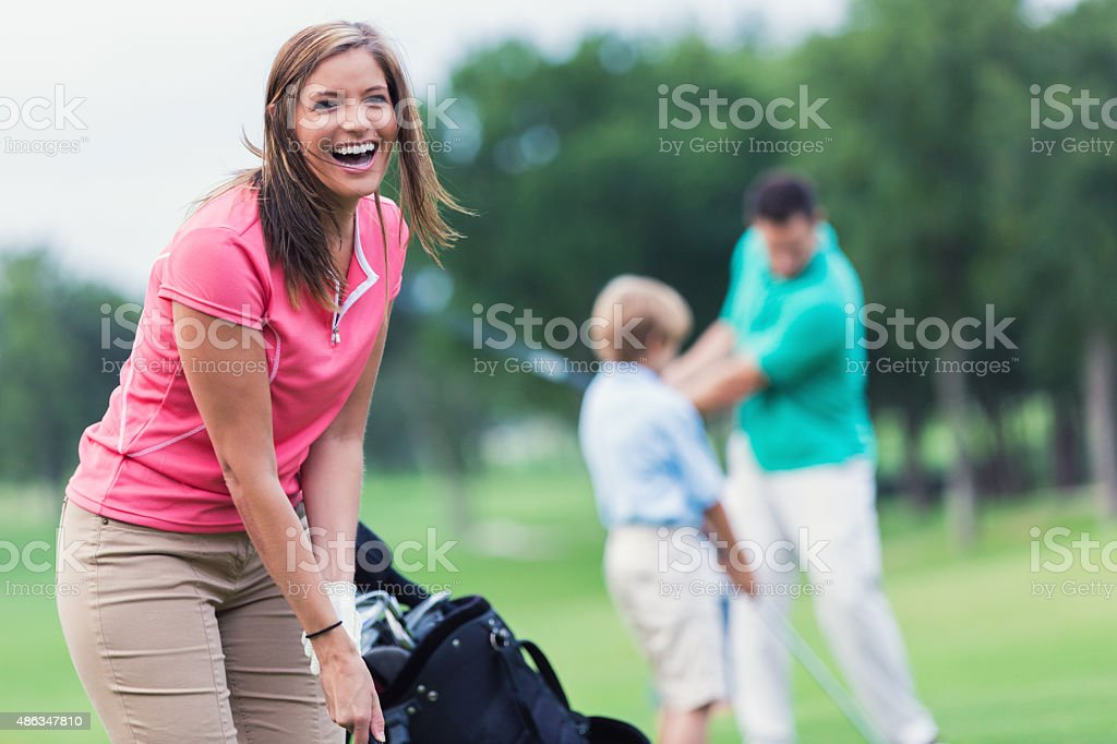 Happy woman playing golf with family on green course stock photo
