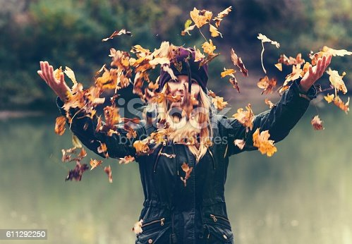 istock Happy Woman playing with autumn leaves raised hands 611292250