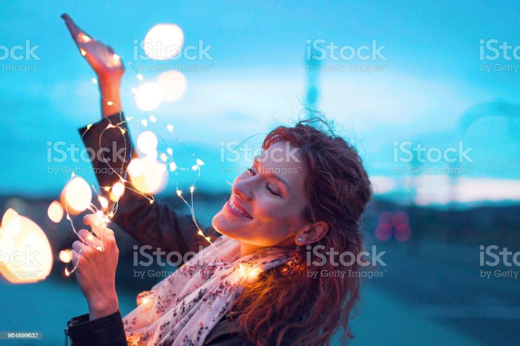 晚上閉著眼睛玩仙女燈花環的快樂女人 - 免版稅一個人圖庫照片
