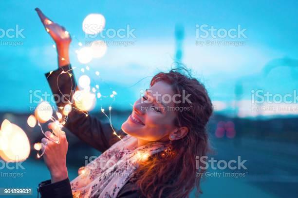 晚上閉著眼睛玩仙女燈花環的快樂女人 照片檔及更多 一個人 照片