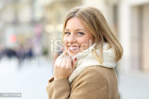 istock Happy woman posing looking at camera in winter in the street 1051172208