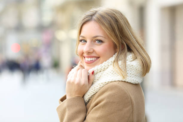 Happy woman posing looking at camera in winter in the street stock photo