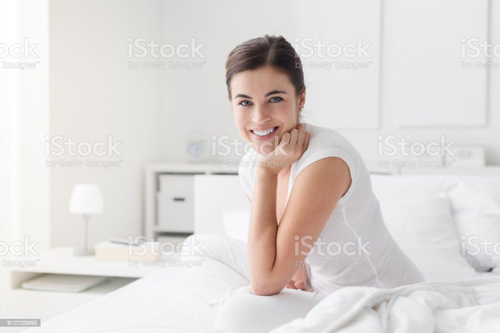 Mujer feliz posando sobre la cama - foto de stock