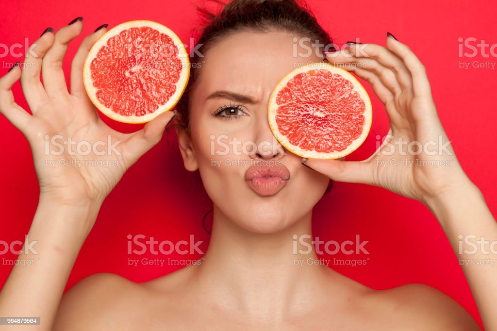 Happy woman posing with slices of red grapefruit on her face on red background royalty-free stock photo