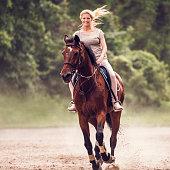 Young smiling woman enjoying while horseback riding and looking at camera.