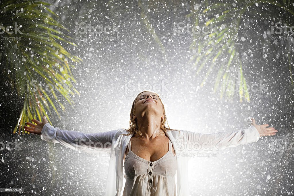 Happy woman praying during tropical rain. stock photo