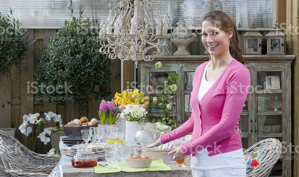 happy woman presenting Easter breakfast picnic table royalty-free stock photo