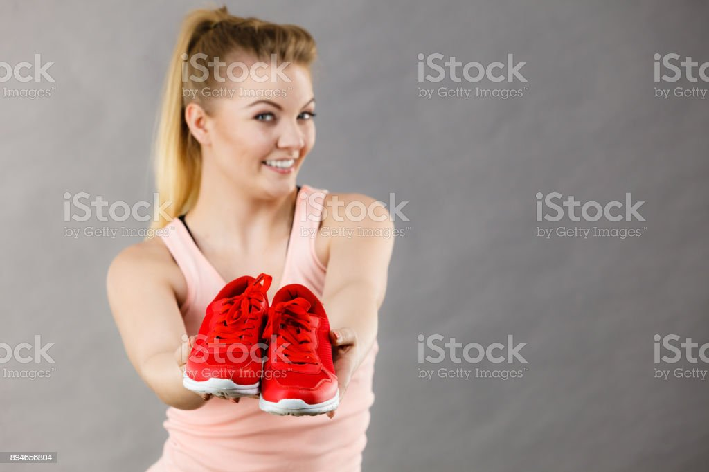 Happy woman presenting sportswear trainers shoes stock photo