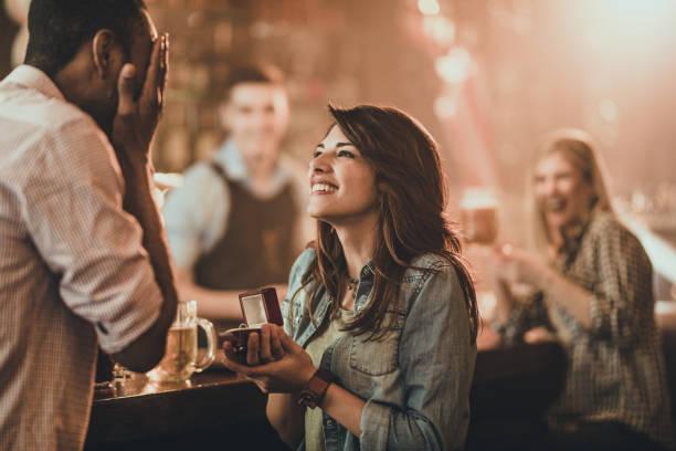 feliz mujer propone a su novio en un bar. - prometido fotografías e imágenes de stock