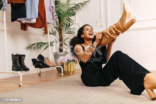 Happy woman pull on knee-high boot on a leg while sitting on a floor