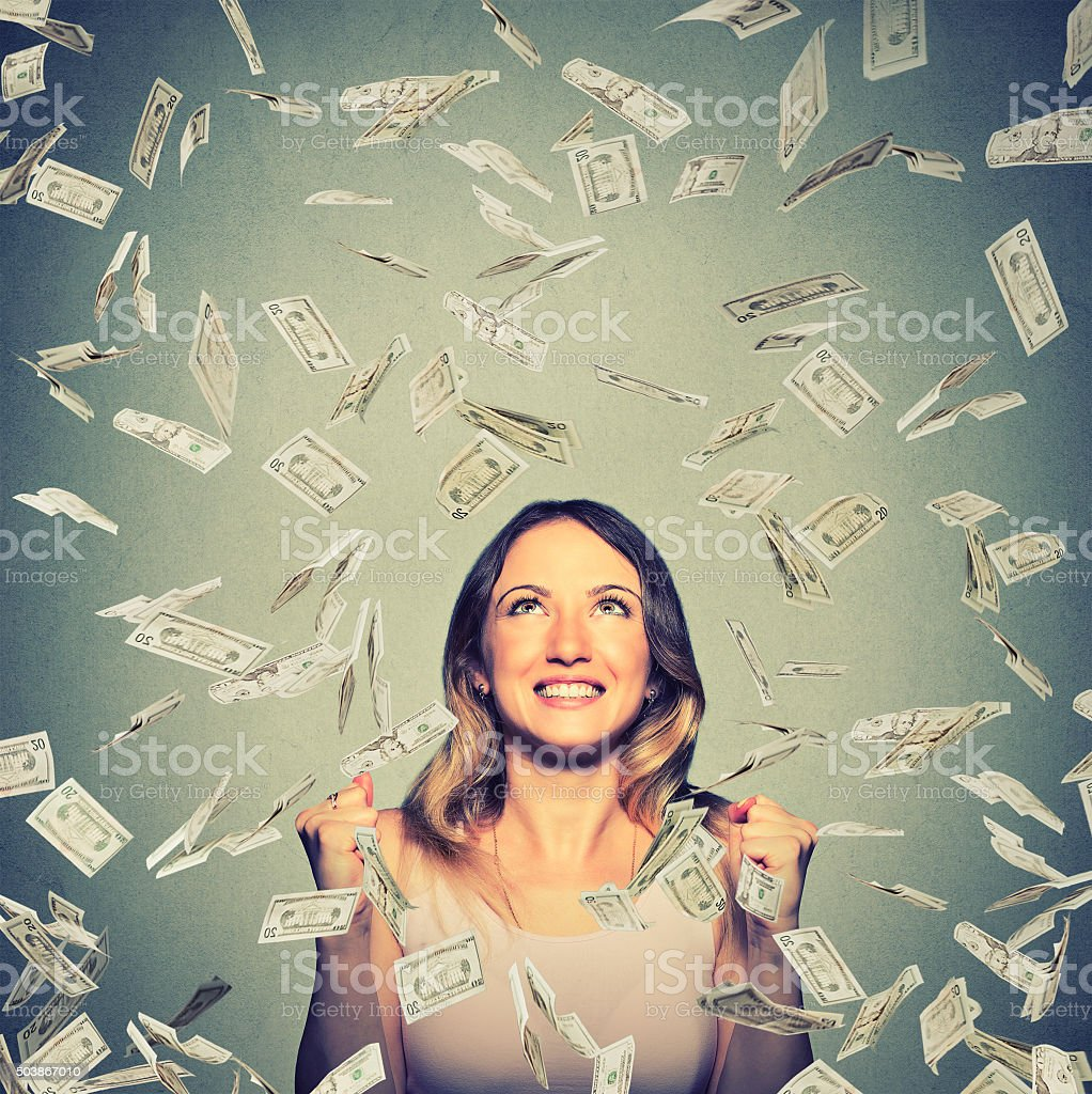 happy woman pumping fists celebrates success under money rain stock photo