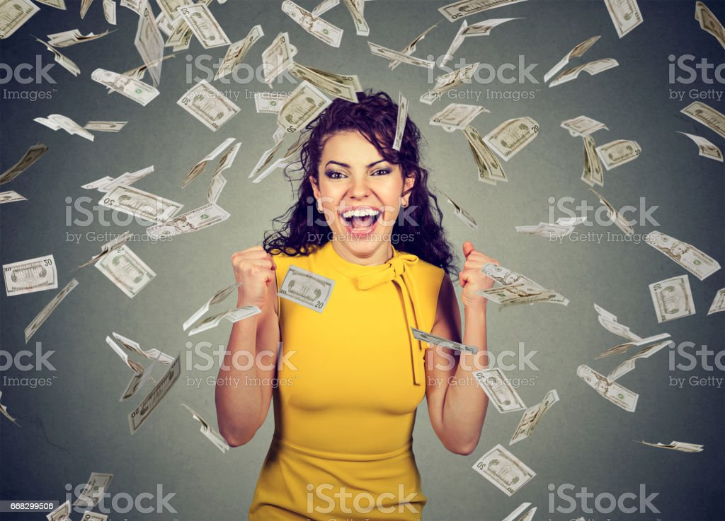 happy woman pumping fists ecstatic celebrates success under a money rain falling down - Photo