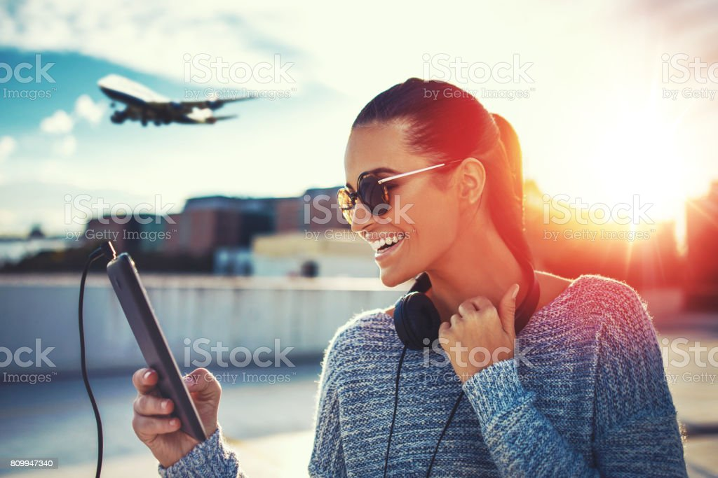 Happy woman purchasing air ticket by tablet stock photo