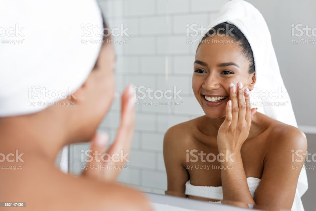 Happy woman putting on facial moisturizer with hand in bathroom mirror stock photo