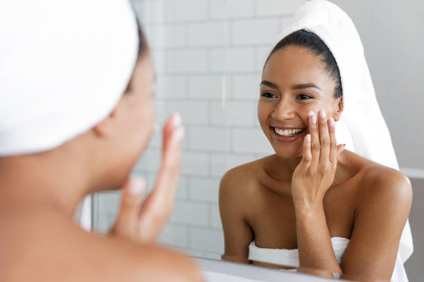 Happy woman putting on facial moisturizer with hand in bathroom mirror Happy woman putting on facial moisturizer with hand in bathroom mirror routine stock pictures, royalty-free photos & images