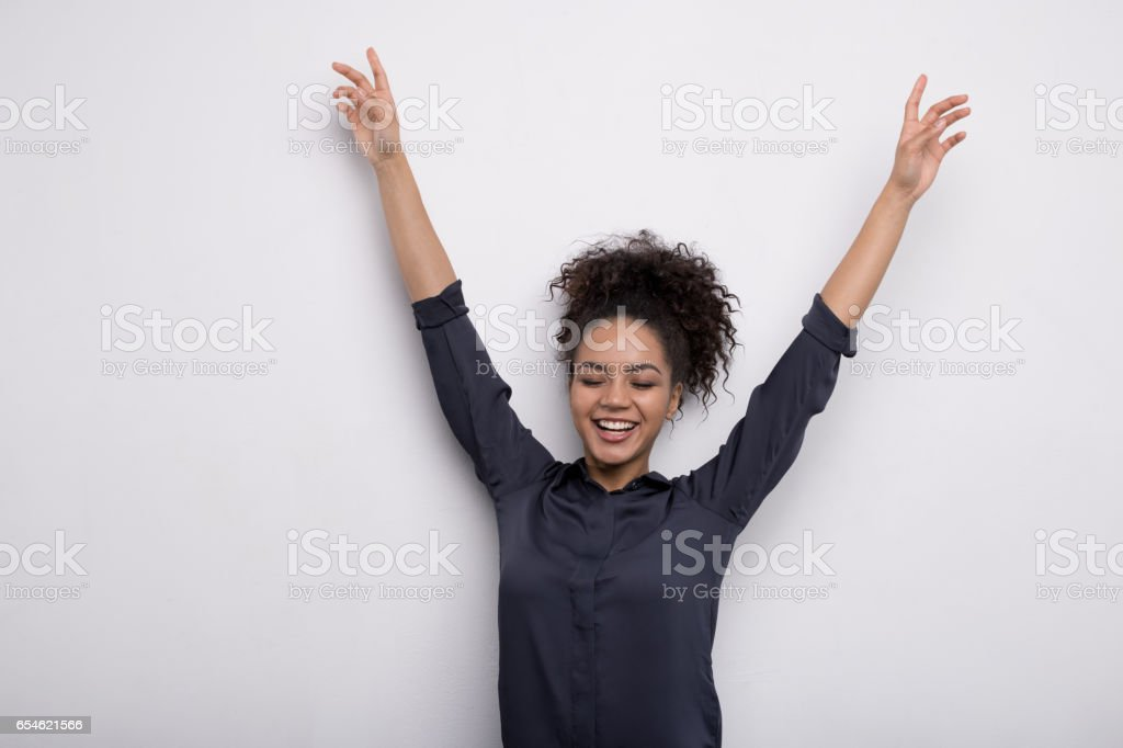 Happy woman raised hands up, wearing a shirt stock photo