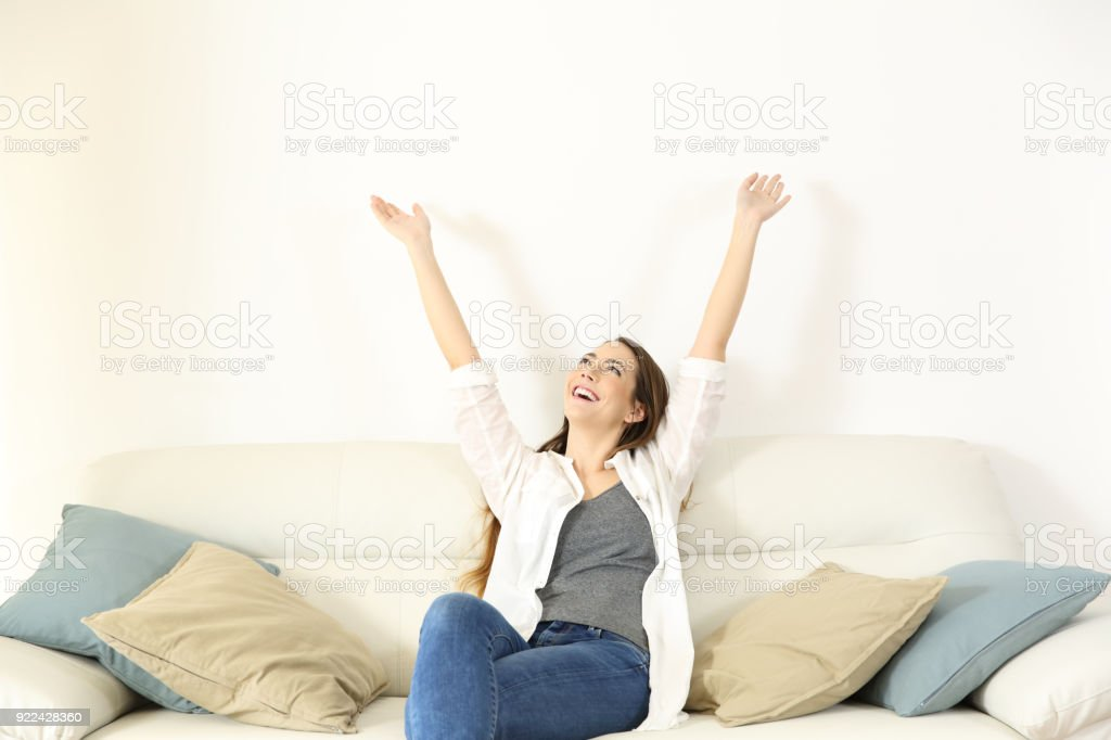 Happy woman raising arms and looking above on a couch stock photo