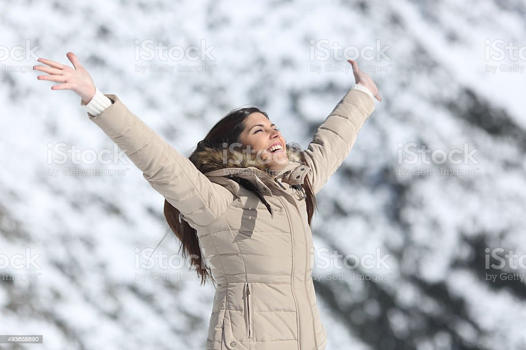 Happy woman raising arms on winter holidays stock photo