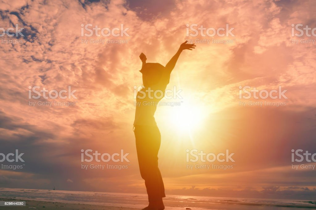 Happy woman raising hands up and beautiful sunrise in background. stock photo