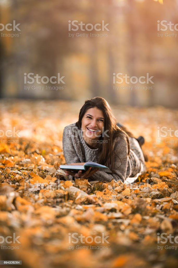 Happy woman reading a book while lying in autumn leaves. stock photo