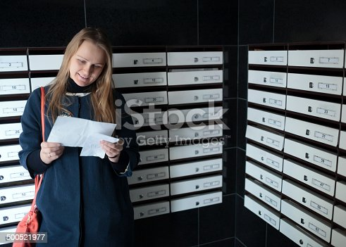 istock Happy woman reading a letter 500521977