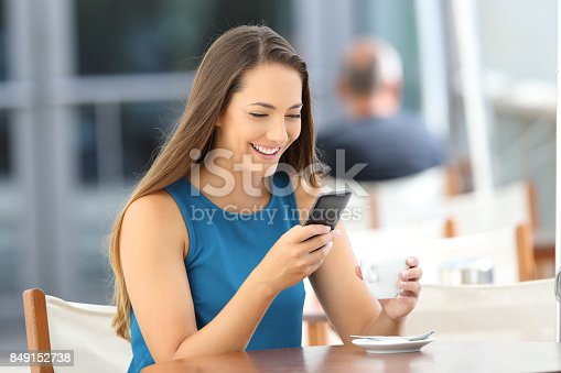 istock Happy woman reading phone message in a bar 849152738