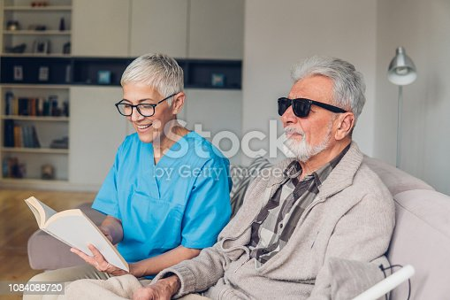 Smiling female caregiver reading to blind patient