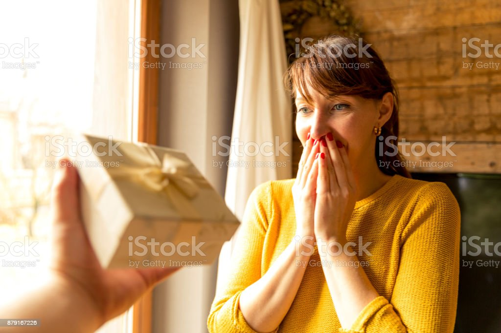 happy woman receiving a gift from husband by a window stock photo