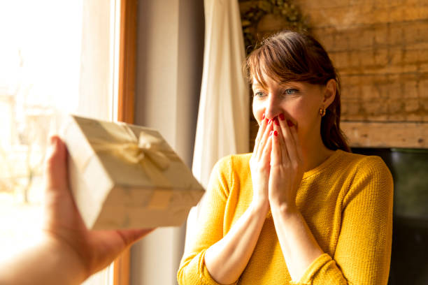 happy woman receiving a gift from husband by a window - receiving stock photos and pictures