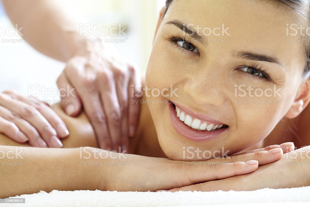 Happy woman receiving a massage on table royalty-free stock photo