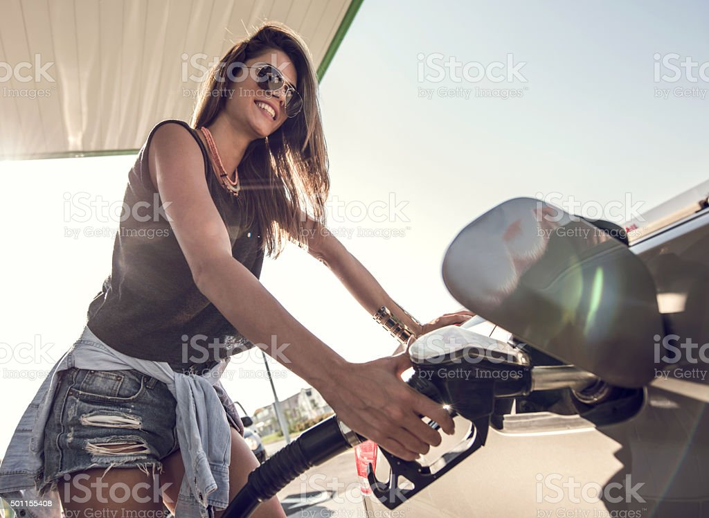 Happy woman refueling the gas tank at fuel pump. stock photo