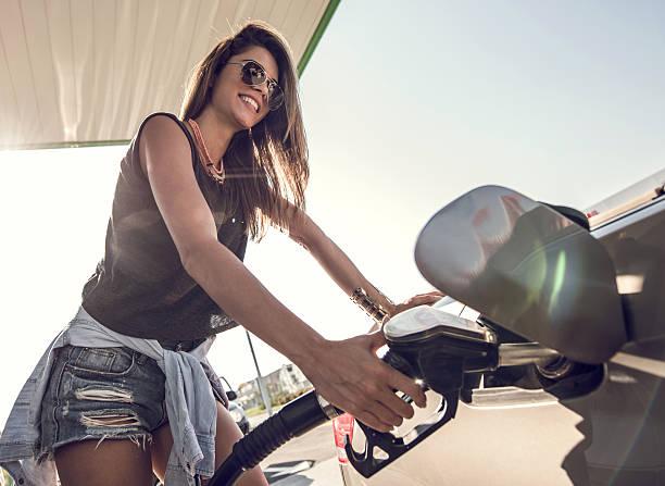mujer feliz echar combustible el tanque de la gasolina en bomba de combustible. - echar combustible fotografías e imágenes de stock