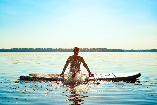 Happy woman relaxes on SUP board and enjoy life