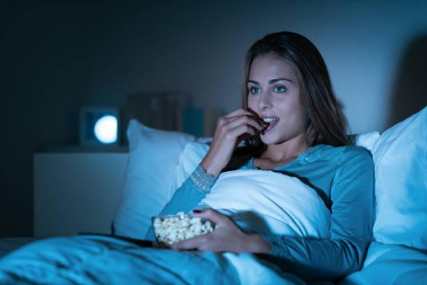 Glückliche Frau im Bett und anschauen von Filmen im Fernsehen spät in der Nacht entspannen, ist sie das Popcorn Essen – Foto